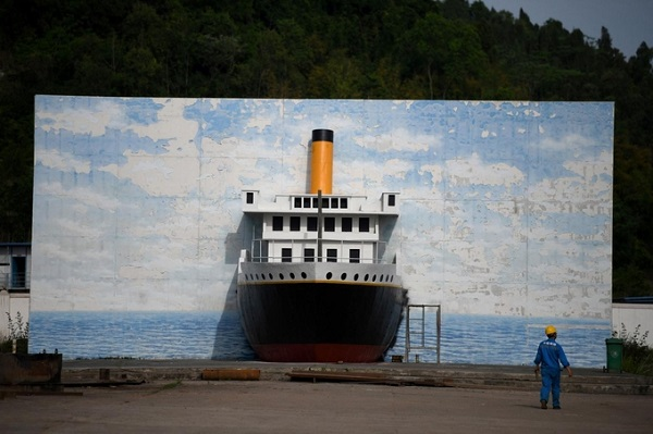 """Công nhân xây dựng đến gần mô hình bản sao Titanic trong công viên ở Tứ Xuyên. Trong lịch sử Titanic là con tàu sang trọng được chủ thầu giới thiệu là """"không thể chìm"""", song nó mãi nằm dưới đáy Đại Tây Dương sau khi va phải một tảng băng trôi. Ảnh: AFP"""